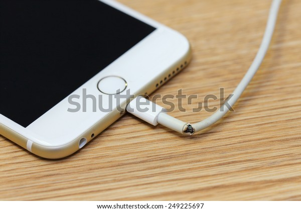 BANGKOK, THAILAND -FEBRUARY 02, 2015: close up image of broken iphone charger cable on the wooden table on February 03, 2015 in Bangkok Thailand.