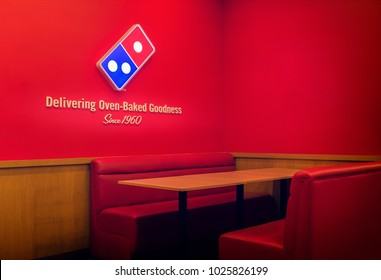 BANGKOK, THAILAND - FEBRUARY 04, 2018 - Domino's Pizza logo and slogan on a red wall over the dining area