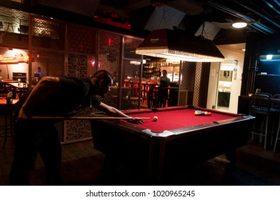 BANGKOK, THAILAND - FEBRUARY 08, 2018: a man aiming his stick at the pool table to play billiard in the bar