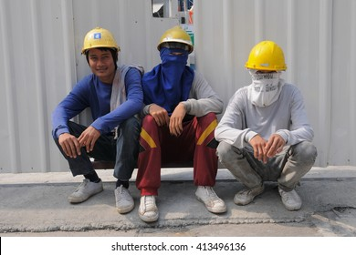 Bangkok, Thailand - February 1, 2011: Migrant workers take a rest on an inner city construction site. The Thai capital has a significant migrant worker population from Burma and Cambodia.