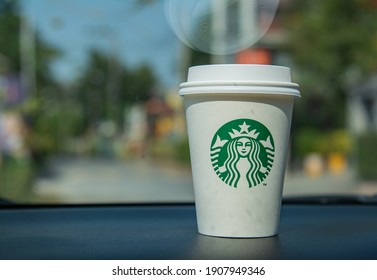 Bangkok, Thailand, February 1, 2021, A woman is drinking a hot latte of the famous coffee shop Starbuck