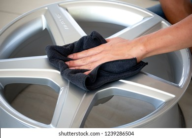 BANGKOK, THAILAND - FEBRUARY 11, 2015; Male hand holding black microfiber cloth cleaning and wiping Mercedes Benz AMG mag and rims after wheel polishing and coating. Car detailing and car wash concept