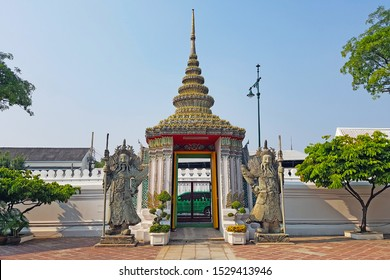 BANGKOK - THAILAND, FEBRUARY 11, 2018: Gate of the Wat Pho Buddhist Temple. At the entrance, stone statues depicting bearded creatures in hats are the guardians of the temple.