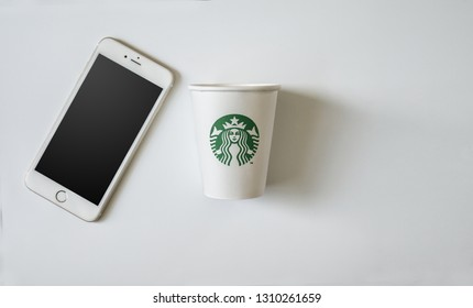 Bangkok ,Thailand - February 11 2019 : A flat lay of Starbuck coffee cup with iPhone 6s plus on white background.
