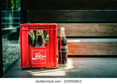 BANGKOK, THAILAND - February 11, 2019 : Vintage Coca Cola Bottle In Red Plastic Box On Wooden Floor At Bangkok Thailand, Coca-Cola Is One of The Most Popular Soft Drinks Brands Around The World.