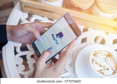 Bangkok, Thailand - February 12,2017:Using PayPal on iPhone. PayPal is a worldwide online payment system and one of the most popular ways of making payment on the Internet.
