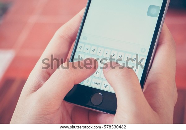 Bangkok, Thailand - FEBRUARY 13, 2017: Hands Holding a Smartphone While Texting