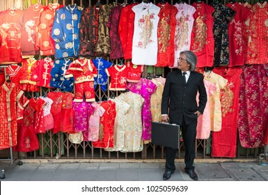 BANGKOK, THAILAND, February 14 2018 : Businessman standing in front of traditional Chinese clothes hang for sale on the Chinese New Year time
