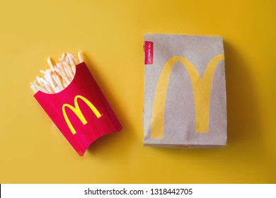Bangkok ,Thailand - February 14 2019 : McDonald's French fries in the French fries box with McDonald's bag on yellow background. McDonald's Corporation is the world's largest fast food restaurant.