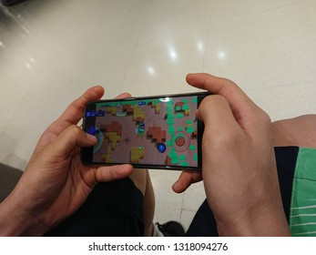 Bangkok, Thailand. February 15, 2019 - teenager boy playing game on smartphone in shopping mall.