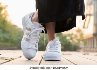 BANGKOK, THAILAND - FEBRUARY 17, 2018 : Women wearing Adidas Superstar W white/gold shoes on nature sunset with popular fashion for woman in Thailand.