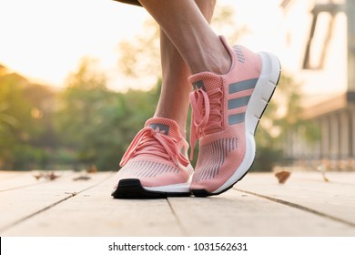 BANGKOK, THAILAND - FEBRUARY 17, 2018 : Women wearing adidas swift run w 2017 sports shoes for running for women on street outdoor - illustration editorial