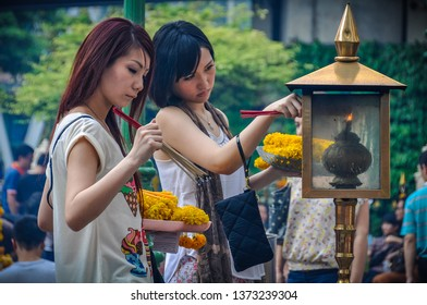 BANGKOK, THAILAND - FEBRUARY 18, 2013: Thai girls lighting a candle in Erawan Shrine in the city of Bangkok in Thailand