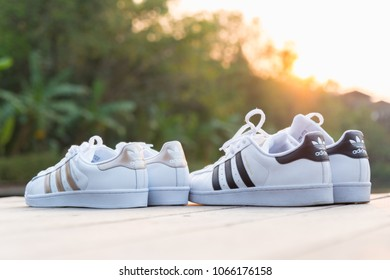 BANGKOK, THAILAND - FEBRUARY 18, 2018 : Couple Adidas superstar  white/black and superstar W white/gold shoes on nuture sunset with romantic fashion concept in Thailand.