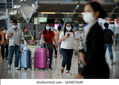 Bangkok, Thailand - February 18, 2020: Air travelers wearing masks walk through departures hall of Suvarnabhumi Airport. Thailand has been assessed as most at risk of Covid-19 virus outside of China.