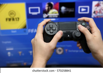 BANGKOK, THAILAND -FEBRUARY 2, 2017: Hand Playing Sony Dualshock 4 Controller for PlayStation 4 with the Screen on February 2,2017