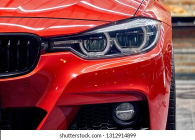 BANGKOK, THAILAND - FEBRUARY 2, 2019: Headlight of BMW 3 series modern sporty sedan with reflection on fender red paint after paint polishing and coating. Illustration of car detailing and restoration
