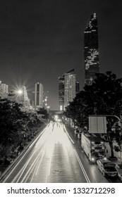 Bangkok, Thailand ; February 2, 2019 : The black and white traffic light trails at night located at King Power Mahanakhon.