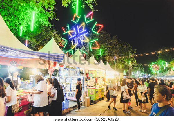BANGKOK, THAILAND - February 2018 - People and tourist enjoying street food festival at night, market stalls, walking, buying food. Food event decorate with colorful neon light in cool design shape.