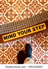 "BANGKOK, THAILAND. FEBRUARY, 2019: the woman wears running shoes Nike Odyssey React,  standing on the retro mosaic tiles with ""mind your step"" caution."