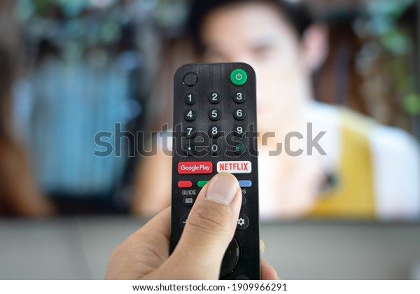 Bangkok, Thailand - February 2021 : Action of human's finger is pressing a netflix button on TV remote control, watching movie series during stay at home.