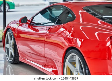 BANGKOK, THAILAND - FEBRUARY 21, 2019: Shiny red Ferrari F430 supercar with reflection on paint. Luxury sports car after ceramic coat. Car detailing & premium garage concept. Automotive background.
