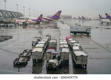 Bangkok Thailand, February 23 2018:  Cargo carts lined up and waited for contained to Thai airway aircraft at Suvarnabhumi International Airport amidst heavy rain atmosphere, Bangkok Thailand.
