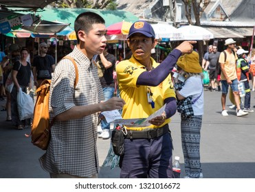 BANGKOK, THAILAND - February 23, 2019 : Asian man tourist asking security guard for direction and information at Chatuchak weekend market.