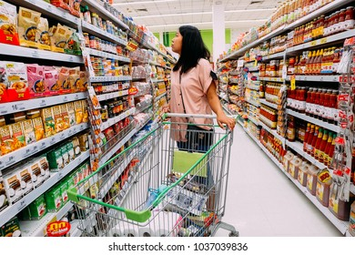 Bangkok, Thailand - February 25, 2018: Woman looking at product at grocery store and reading product information. BigC supermarket interior view. BigC is a large supermarket chain in Thailand.