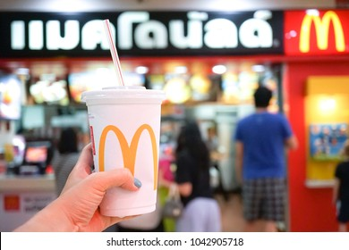 Bangkok, Thailand - February 25, 2018 : A closed up photo of a hand holding a cup of Coca Cola drink in front of McDonalds shop. Thai text translated as McDonalds. Editorial use only.