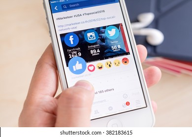 Bangkok, Thailand - February 26, 2016: Hand holding iPhone with New facebook like button (6 emoji) on screen ,Social media are using for information sharing and networking.