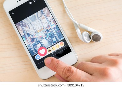 Bangkok, Thailand - February 26, 2016: Hand holding iPhone with New facebook like button (6 emoji) on screen ,Social media are using for information sharing and networking