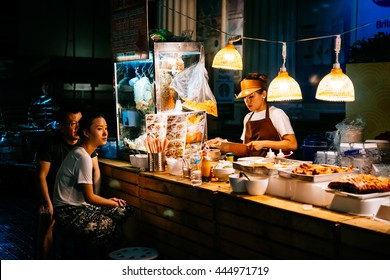 BANGKOK, THAILAND - FEBRUARY 26, 2016: People are buying food at night street food market in Bangkok, Thailand.