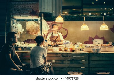 BANGKOK, THAILAND - FEBRUARY 26, 2016: People are buying food at night street food market in Bangkok, Thailand. Toned picture
