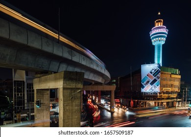 Bangkok / Thailand - February 26 2020: A BTS Skytrain travels past the Park Nam Tower at night.