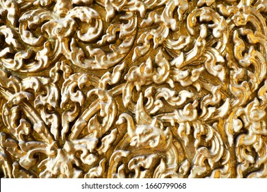 BANGKOK, THAILAND -February 29, 2020: Wood carving with gold painting and glass mosaics on the wall at Wat Bowonniwet