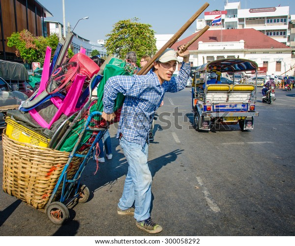 BANGKOK, THAILAND - FEBRUARY 5, 2015: Man pulling a cart loaded with goods crosses a busy street in Chinatown.