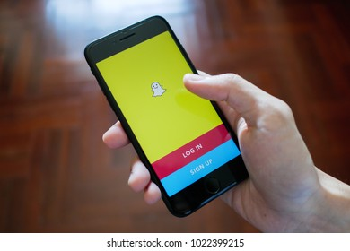 Bangkok, Thailand - February 6, 2018 : Apple iPhone 7 held in one hand showing its screen with Snapchat application.