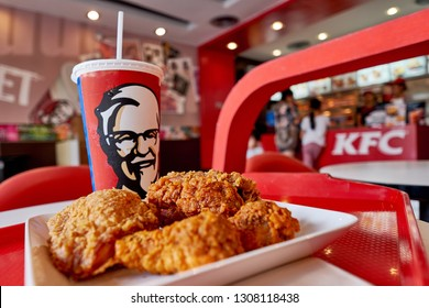 BANGKOK, THAILAND- FEBRUARY 6, 2019 : Crispy fried chicken and cup of drink served in retail background of KFC restaurant. KFC is popular fast food chain known as Kentucky Fried Chicken.