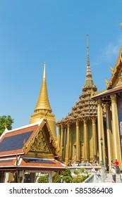 BANGKOK, THAILAND - FEBRUARY 8, 2017: Prasat Phra Thep Bidon and Golden Stupa with tourists at Temple of the Emerald Buddha (Wat Phra Kaew), Grand Palace complex, Bangkok, Thailand