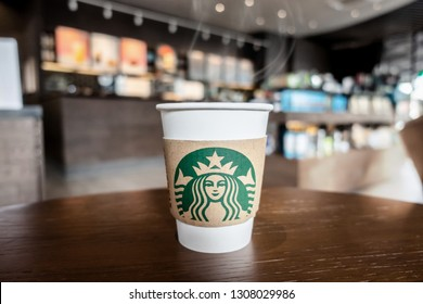 Bangkok ,Thailand - February 8 2019 : A cup of take home Starbucks espresso   coffee with holder on the table in the Starbucks coffee shop.