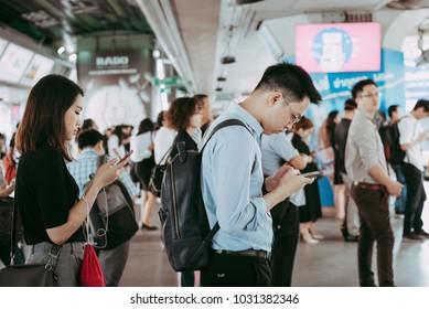 BANGKOK THAILAND FEBUARY 20, 2018: Passenger at BTS Skytrain station in Bangkok Thailand, everybody  looking down at smartphone while waiting for the BTS skytrain.