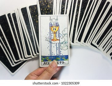 Bangkok, Thailand: Fortuneteller holding Ace of cups (one cup) tarot card surround with other cards.(This Tarot Card have good meaning it's about your wishes will come true.) :Picture on 30 Dec 17