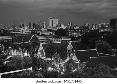 Bangkok, Thailand. Illuminated historical houses in the center of Bangkok, Thailand. Tall skyscrapers at the background at night. Black and white