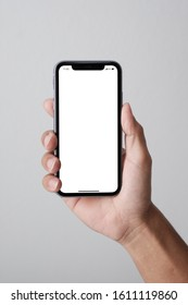 Bangkok, Thailand - JAN 10, 2019: Studio shot of Hand holding Smartphone iPhone 11 Pro Max and Show white screen for your web site design, logo, app   - include clipping path.