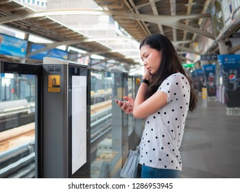 BANGKOK THAILAND, Jan 1,2019 : Asian woman passenger using smartphone and social media in train station. Cute Thai girl waiting for skytrain on BTS Skytrain station. The Bangkok Mass Transit System.