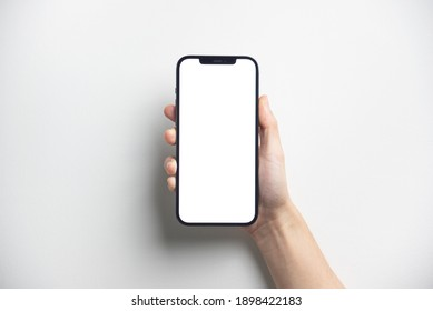 Bangkok, Thailand - Jan 13, 2021: Close up hand holding black smartphone iPhone 12 Pro Max with white screen. Isolated on white background. Mobile phone frameless design concept.