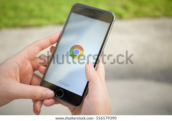 Bangkok, Thailand - Jan 15,2017: Chrome app on the Apple iPhone display screen. Top view of Business workplace.Closeup on a women hands as her is using a smart phone