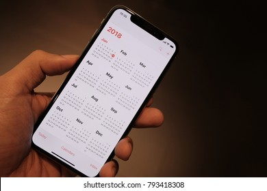 BANGKOK, THAILAND - JAN 15th, 2018: Hand hold iPhone X show calendar of 2018 on screen, iPhoneX was created and developed by the Apple inc.