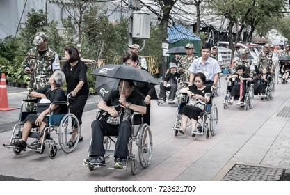 BANGKOK, THAILAND - JAN 16 : Officer help senior on wheelchair to devotions for funeral of King Rama IV at Grand Palace on 16 January 2017 in Sanam Luang, Bangkok, Thailand